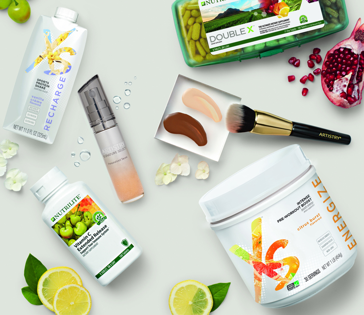 A variety of Amway products including XS, Nutrilite and Artistry, shown with some natural ingredients.