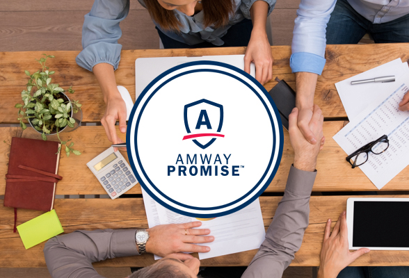 People shaking hands across a table where a group of people are working with notebooks and tablet computers. Amway Promise logo displayed in the center.
