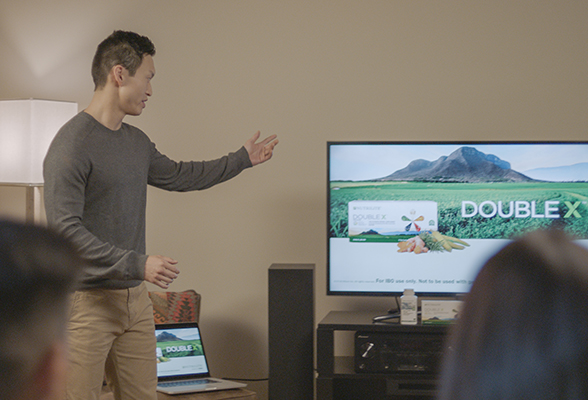 Man pointing to television while teaching others.