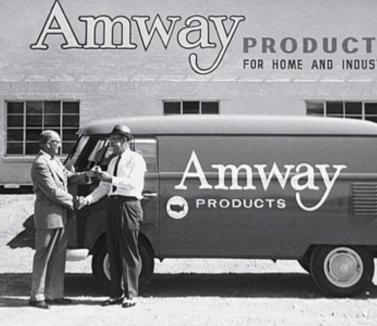 "Historic photo of Amway building with text ""Amway Products for Home and Industry"" and Amway van."