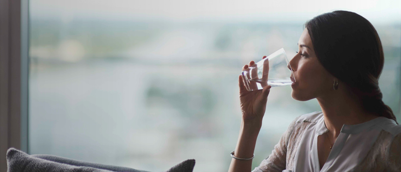 Woman drinking a glass of water next to a window.