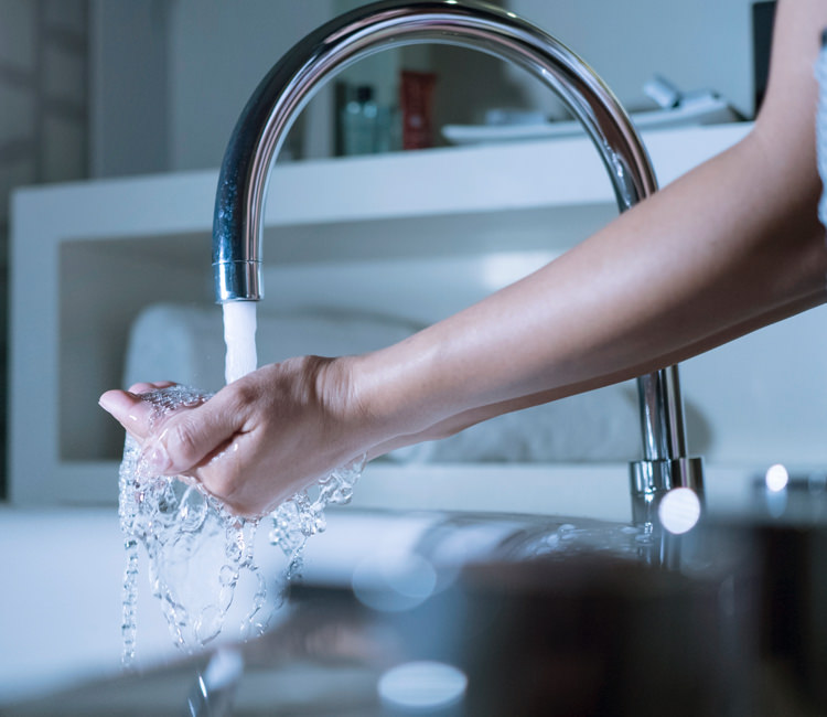 Woman running her hand under tap water from a kitchen sink faucet.