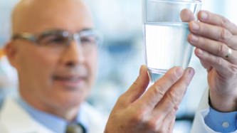 Our Technology: Cleaner water, with ease. Background image shows man in a lab examining a glass of water.