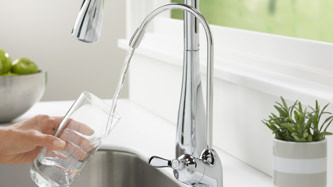 Water Treatment: Purified water, straight from the tap. Background image shows a someone filling a water glass from the chrome faucet of an eSpring™ water treatment system.