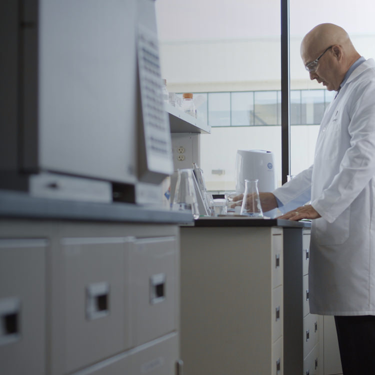 Research scientist in a lab working with an eSpring™ above the counter unit.