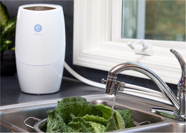 eSpring™ water purifier connected to a kitchen faucet, washing vegetables.