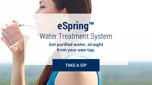 eSpring™ Water Treatment Systems: Get purified water, straight from your own tap. Take a sip. Background image showing a woman drinking a glass of water.