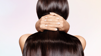 Care: Cleanse and condition. Background image shows back of woman's head with long brown hair.