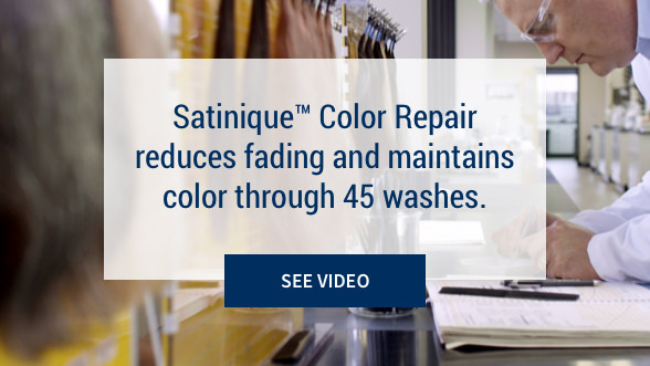 Satinique™ Color Repair reduces fading and maintains color through 45 washes: See Video. Background image shows research scientist taking notes in a lab with hair samples in front of him.