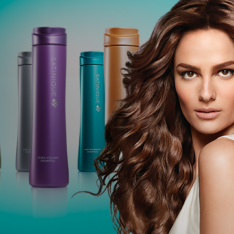 A woman with wavy styled hair and Satinique™ shampoo bottles from each of the care systems.